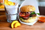 Обои Бургер в бумажной салфетке лежит рядом с соусом и стаканом с запеченным картофелем