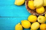 Обои Желтые лимоны в плетенной корзинке на голубой древесине
