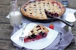 Обои Кусок черничного пирога на белой тарелке с вилкой, рядом стоит баночка с молоком и трубочкой и остальная часть пирога