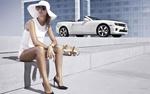 Обои Девушка в белом платье сидит на ступеньках, у здания на фоне кабриолета Chevrolet Camaro / Шевроле Камаро