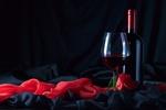Обои Бокал с вином, бутылка и роза на черной и розовой ткани