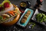 Обои Японская кухня: суши-ассорти, васаби и имбирь на циновке, нарезанные овощи в миске со льдом, рядом роллы и бобы в черных тарелках