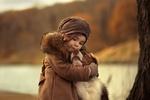 Обои Девочка обнимает собаку на фоне осенней природы