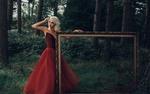Обои Девушка-блондинка в красном платье стоит с рамкой для картины в лесу