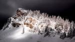 Обои Скала с растущими деревьями, покрытая снегом и освещаемая светом в ночи