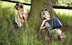 Обои Мальчик играет на гармошке лежа под деревом, а девочка наблюдает за ним