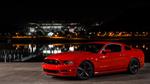 Обои Красный Ford Mustang на фоне города у воды