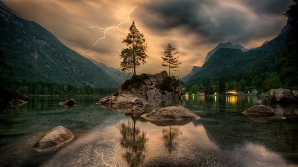 Деревья на горных образованиях среди воды, на фоне молнии в небе над горами, фотограф jplenio