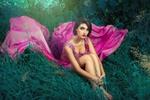 Обои Брюнетка в платье с лиловым шлейфом сидит на траве, обхватив ноги, by Cristian Newman