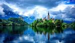 Обои Церковь Успения Девы Марии на Бледском озере в городе Блед в Словении / Slovenia на фоне грозового неба