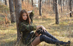 Обои Девушка в камуфляжной куртке сидит возле дерева в осеннем лесу