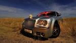 Обои Автомобиль Chrysler стоит в поле с черепом на капоте