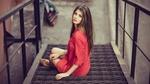 Обои Девушка в красном платье сидит на металлической лестнице