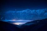 Обои Огни света в долине, среди заснеженных гор, покрытые ночным туманом, работа Сириус на горном хребте, автор Shinichiro Saka