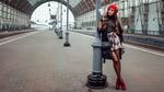 Обои Симпатичная брюнетка в ярком берете позирует, прислонившись к фонарному столбу, на перроне вокзала