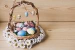 Обои Пасхальная корзинка с крашенными яйцами, игрушечными зайчиками в венке из ромашек стоит на деревянной поверхности