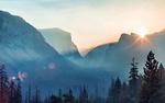 Обои Туманные горы, покрытые хвойным лесом, в лучах солнца
