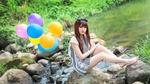 Обои Девушка с разноцветными воздушными шариками сидит на камне около речки