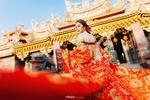 Обои Азиатка китаянка в красном платье стоит в пол-оборота на фоне храма с позолоченной крышей