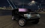 Обои Автомобиль Hummer H2 со спиннерами из игры NFS: Underground 2 на фоне ночных небоскребов города Bayview слева и индустриальных построек справа