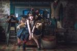 Обои Милая девушка азиатской внешности в черном платье с крыльями летучей мыши, с рогами на голове сидит в кресле