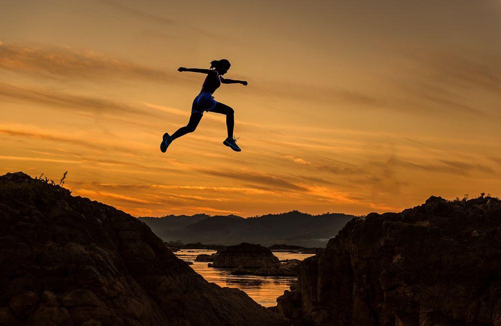 Обои для рабочего стола Девушка в прыжке между каменными образованиями на рассвете, by Sasin Tipchai