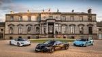 Обои Три авто марки McLaren / Макларен стоят перед двухэтажным зданием