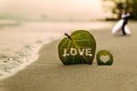Обои Листочек с надписью Lоve / любовь на побережье, где стоят молодожены