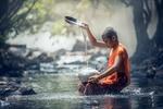 Обои Мальчик-буддист сидит в речке и моет посуду, by Sasin Tipchai