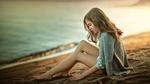 Обои Девочка сидит на песке у моря