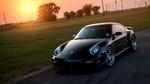 Обои Porsche 911 стоит на дороге на фоне солнца
