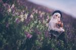 Обои Куколка с букетиком сидит на цветочном лугу