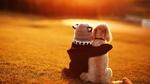 Обои Ребенок, приобняв собаку, сидит на поляне, освещенной солнцем