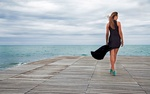 Обои Стройная девушка в черном платье на пирсе перед морским простором