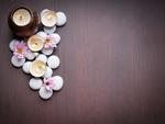 Обои Spa-набор: зажженные свечи, белые камешки и розовые цветы на деревянной поверхности