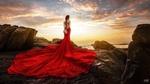 Обои Девушка в красном платье и с букетов за спиной стоит на берегу и смотрит на море