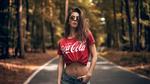 Обои Модель Sara Tessitore в очках и футболке с надписью coca-cola стоит на дороге. Фотограф Martin Kuhn