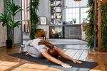 Обои Девушка занимается йогой на коврике в светлой гостиной с комнатными растениями