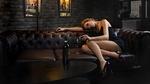 Обои Симпатичная девушка в коротком платье позирует, лежа на диване с бокалом вина