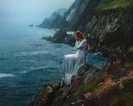 Обои Девушка в длинном платье сидит на обрыве на фоне моря. Фотограф TJ Drysdale