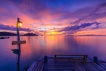 Обои Деревянные мостки и горящий фонарь на фоне заката солнца на море
