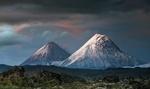 Обои Заснеженная гора и вулкан, по которому стекает лава, под сумрачным небом, фотограф suk eun kim