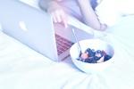 Обои Девушка завтракает и одновременно работает за ноутбуком марки Apple