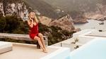 Обои Модель и порнозвезда Nancy A / Нэнси А в красном платье позирует, сидя на деревянной скамейке на фоне природы и гор
