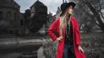 Обои Модель Maia Puchnina / Мария Пучнина в черной шляпе и в красном пальто позирует, стоя на размытом фоне природы и здания. Фотограф Иван Горохов