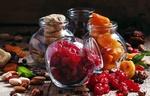 Обои Четыре баночки с курагой, инжиром, черносливом и сушеной вишней среди россыпи орехов, изюма и других сухофруктов
