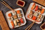 Обои Японская кухня: два блюда с ассорти из суши и роллов рядом палочки для еды соус и циновка
