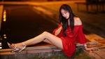 Обои Симпатичная азиатка в красном платье и стройными ногами в туфлях позирует, сидя на бордюрном камне на фоне бассейна