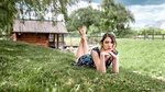 Обои Модель Disha Shemetova / Диша Шеметова в легком летнем платье позирует, лежа на траве, на размытом фоне деревьев и деревяного дома