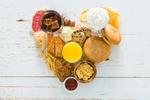 Обои Вид сверху на завтрак в форме сердца из кофе, чая, апельсинового сока, хлопьев, бутербродов, печенья, конфет и зефира